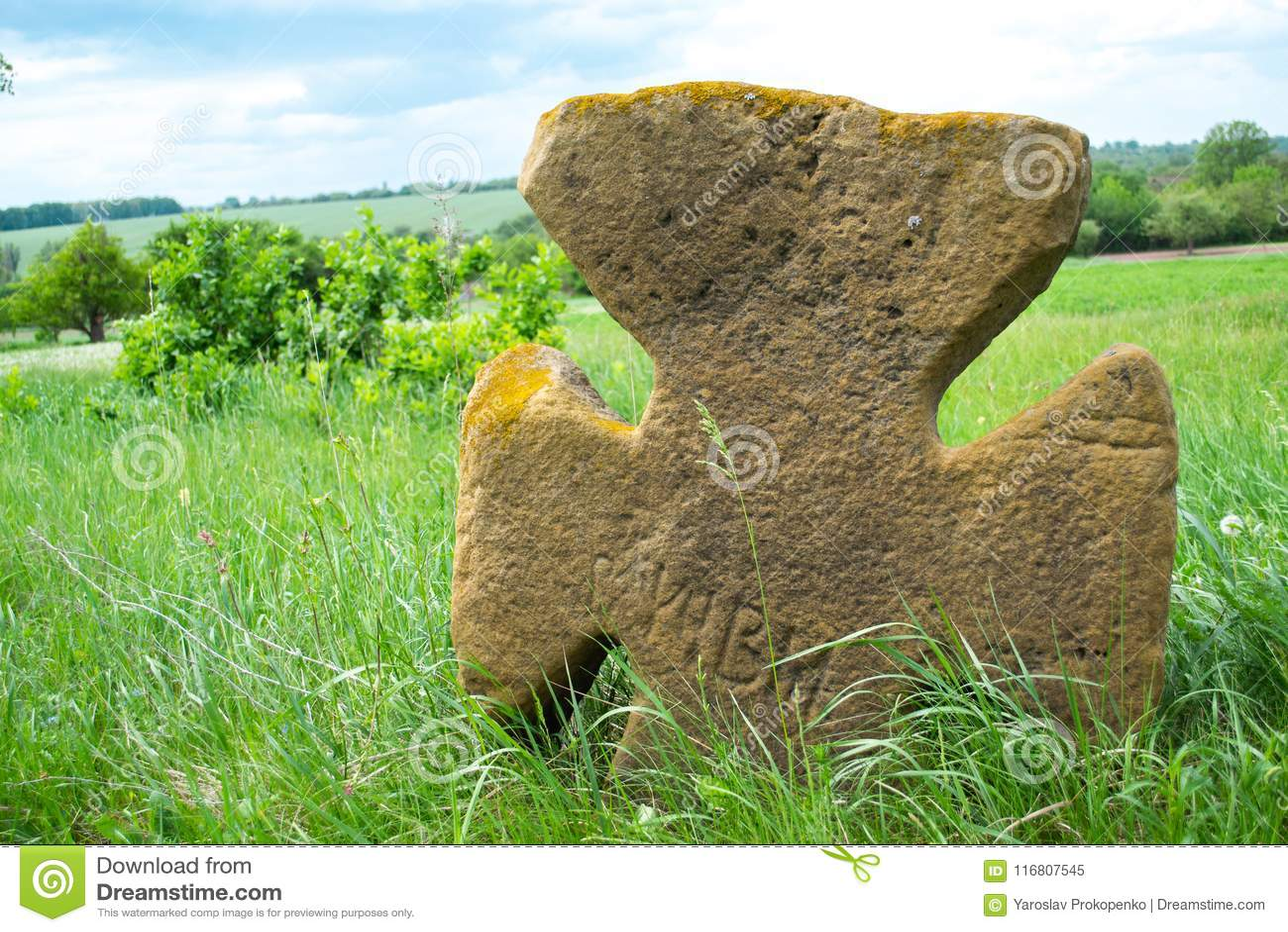 Vecchio incrocio di pietra su un prato verde