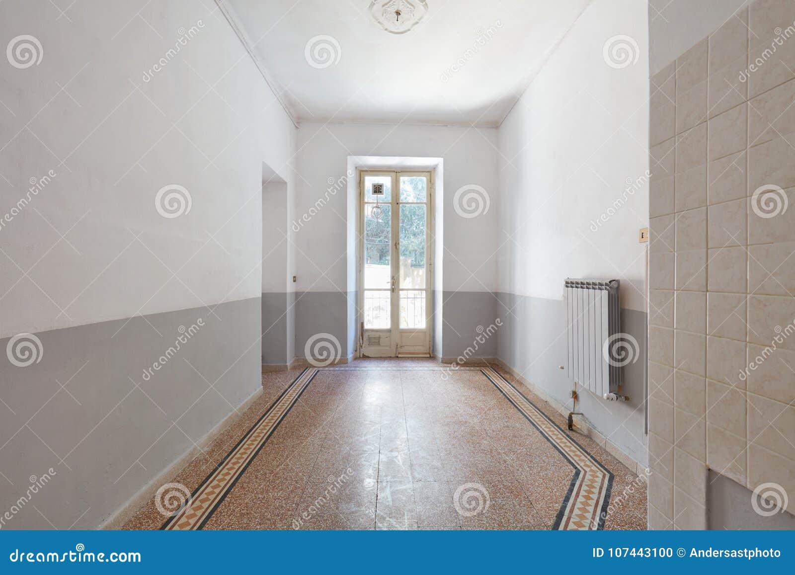 Vecchio, interno vuoto della stanza con la finestra e pavimento piastrellato