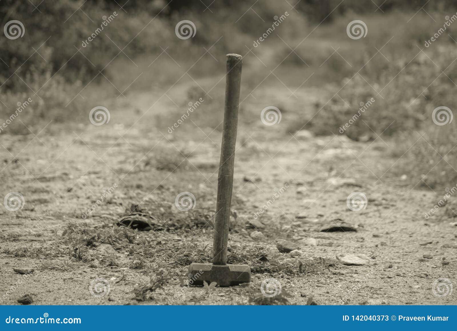 Vecchio martello sulla terra con la maniglia di legno