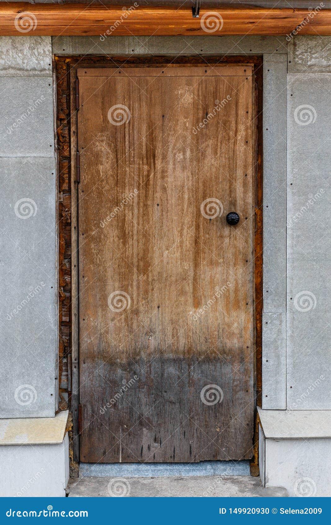 Vecchio portello di legno chiuso Una sbucciatura, porta incrinata e marrone chiaro
