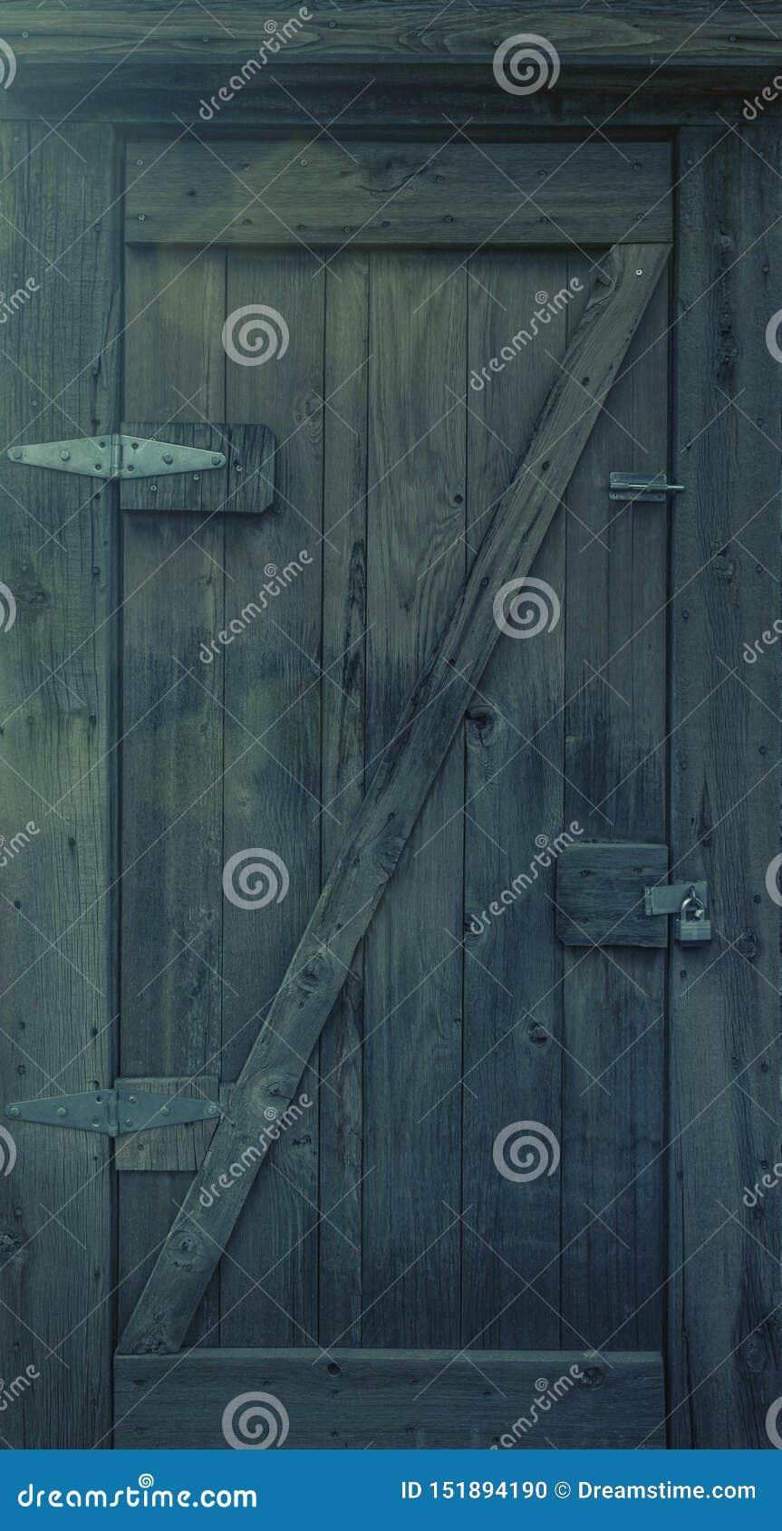Vecchio portello di legno con il lucchetto