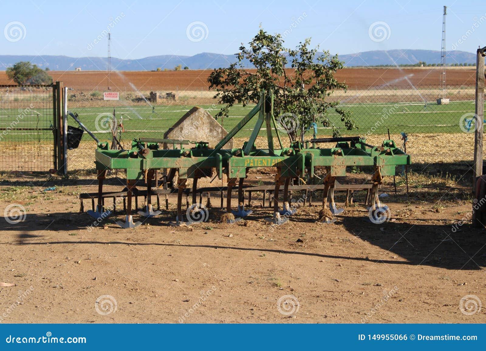 Vecchio rastrello del trattore in un prato