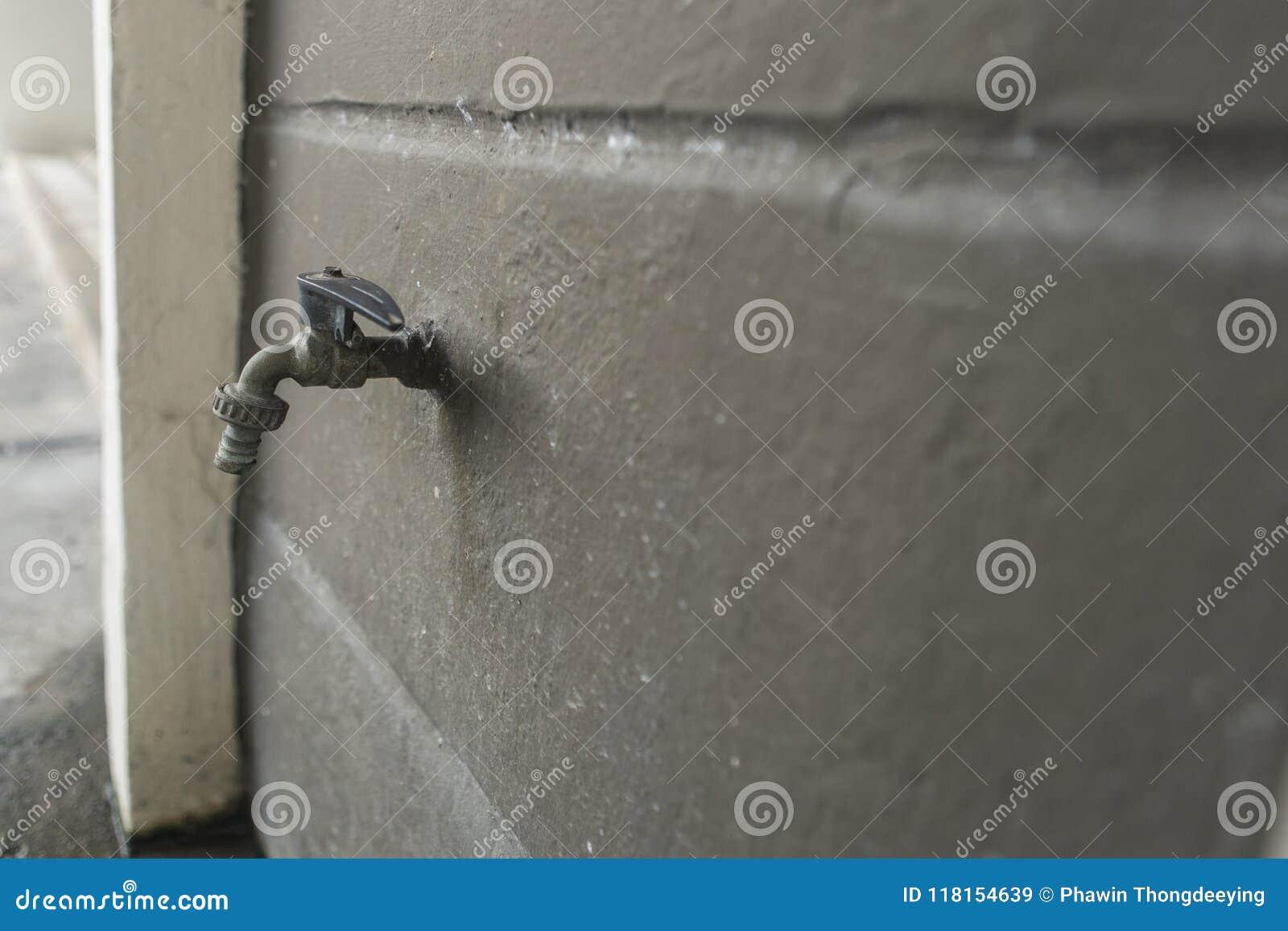 Vecchio rubinetto grigio sul muro di cemento