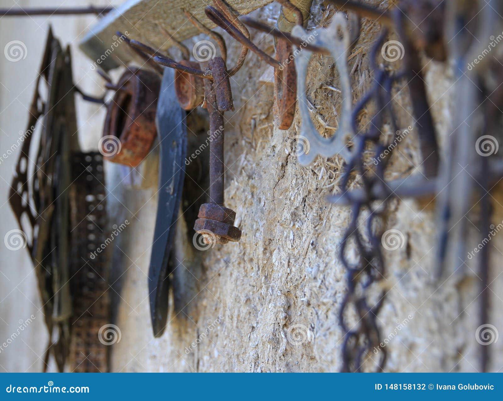 Vecchio strumento arrugginito su un vecchio gancio del gancio