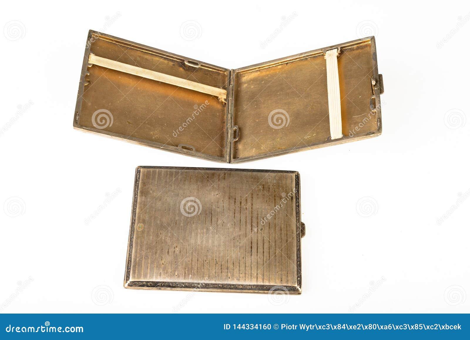 Vecchio tabacco-tubo del metallo su una tavola bianca Le sigarette antiquate imballano
