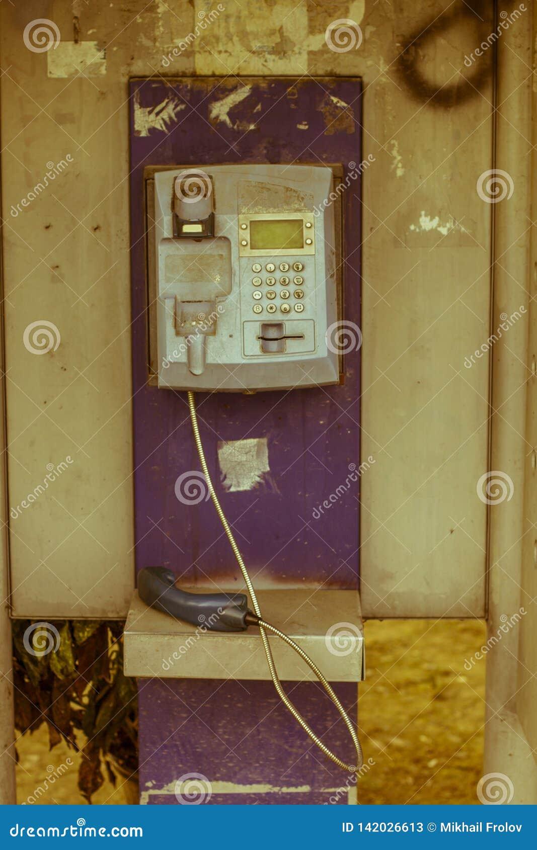 Vecchio telefono a gettone fuori servizio nella città