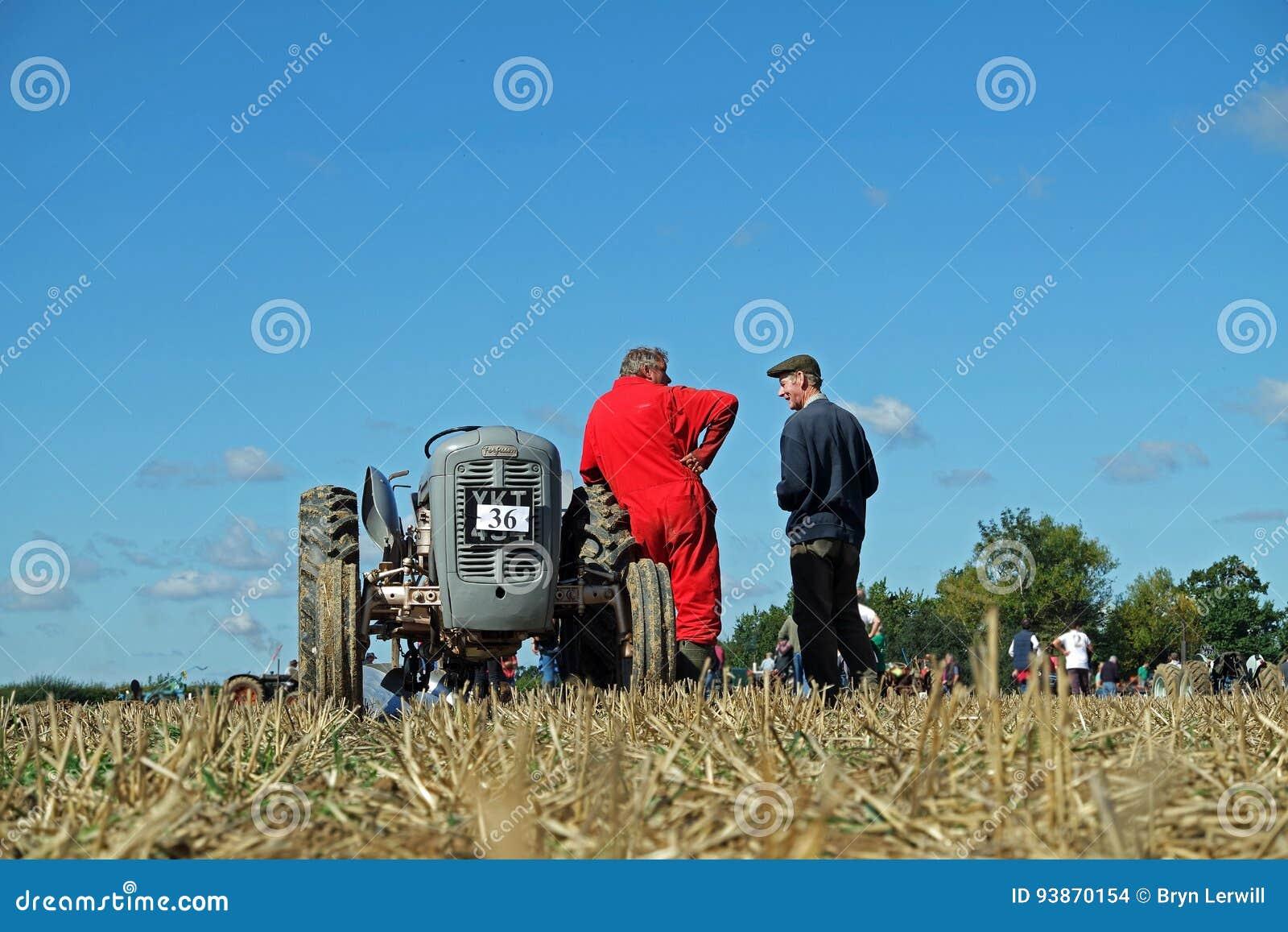 Vecchio trattore grigio di Ferguson e driver adatto rosso