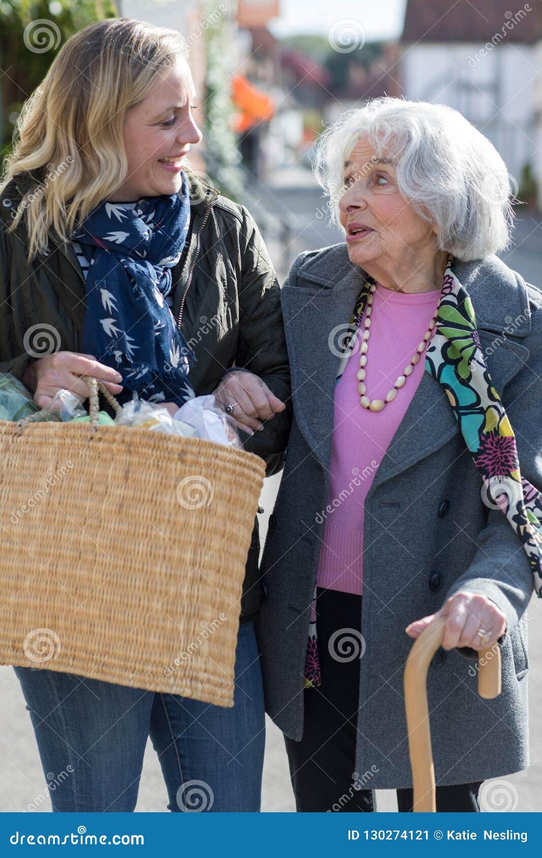 Vecino maduro que ayuda a la mujer mayor a Carry Shopping