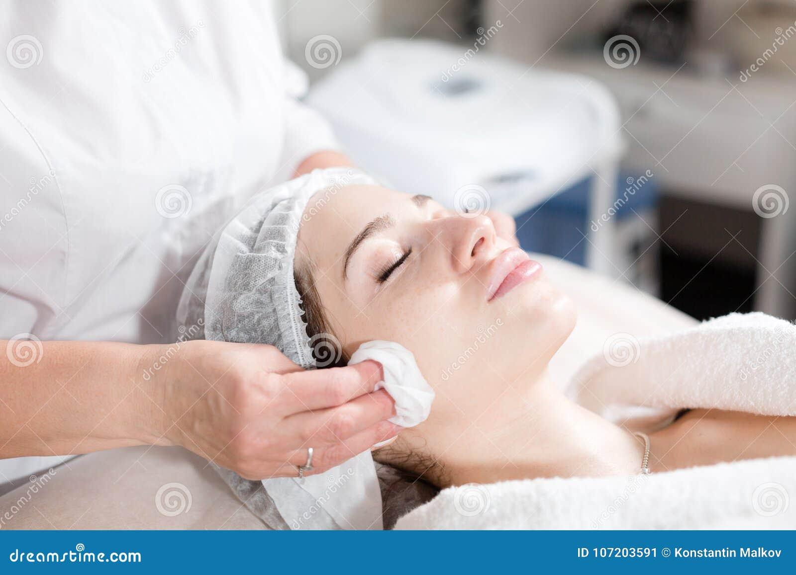 Veeg met steriel servetgezicht af Jonge mooie vrouw die behandelingen in schoonheidssalons ontvangen Het gezichts het reinigen sc