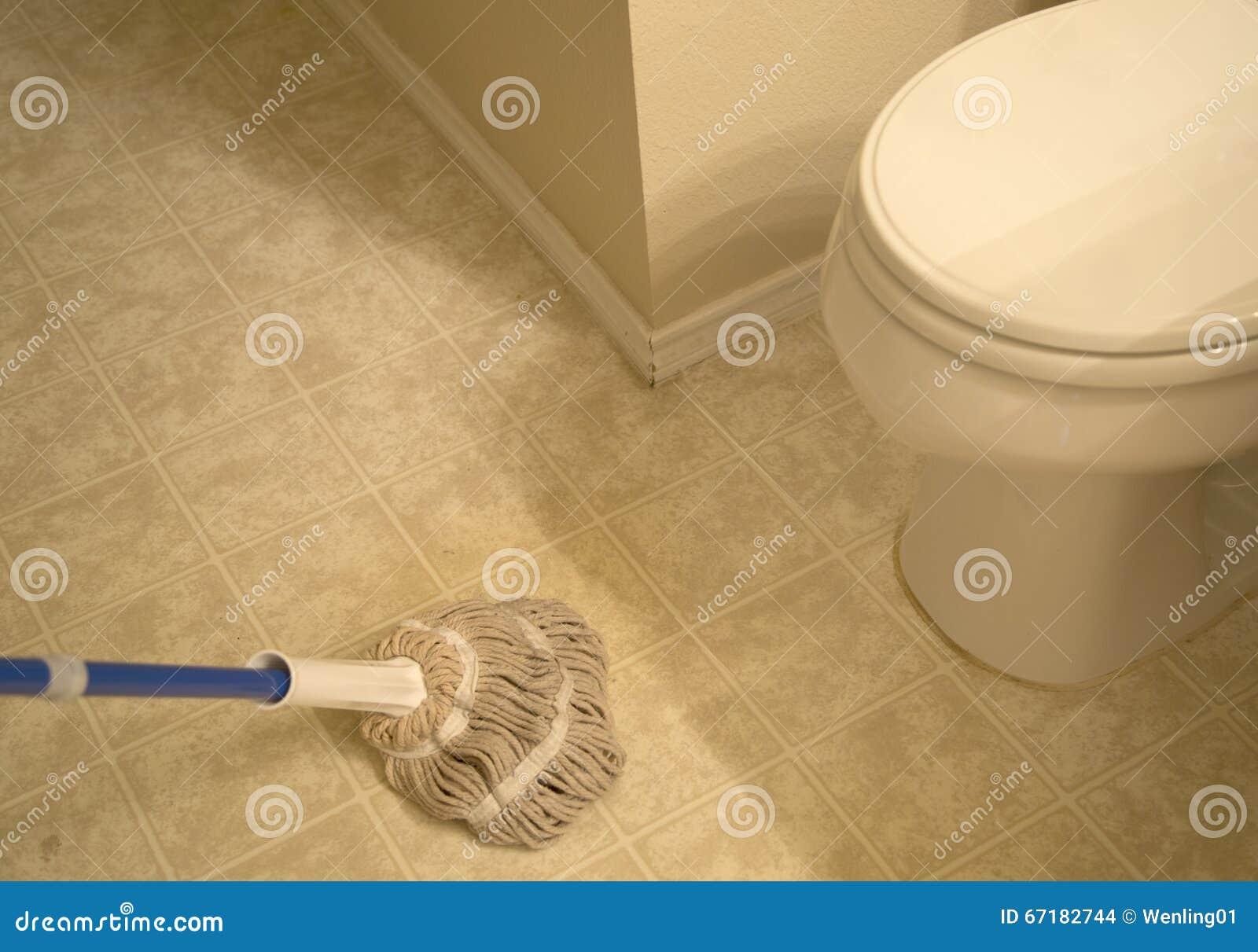 Veegde de badkamers betegelde vloer met zwabber af stock foto