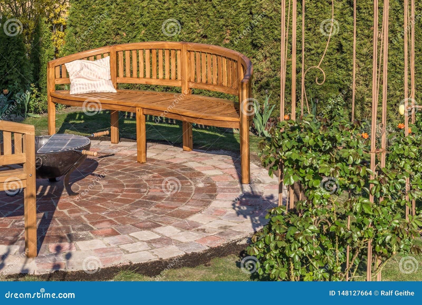 Veel liefs ontworpen tuin met steencirkel, houten banken en brandkom