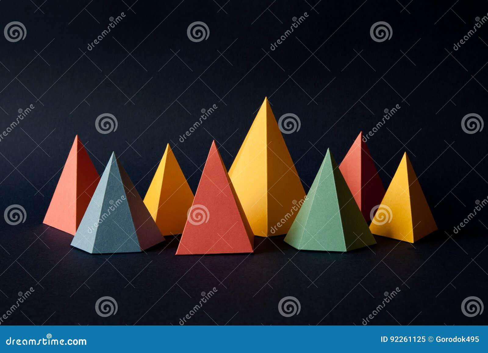 Veelkleurige geometrische abstracte achtergrond De heldere cijfers van de de driehoeksvorm van de prismapiramide aangaande donker