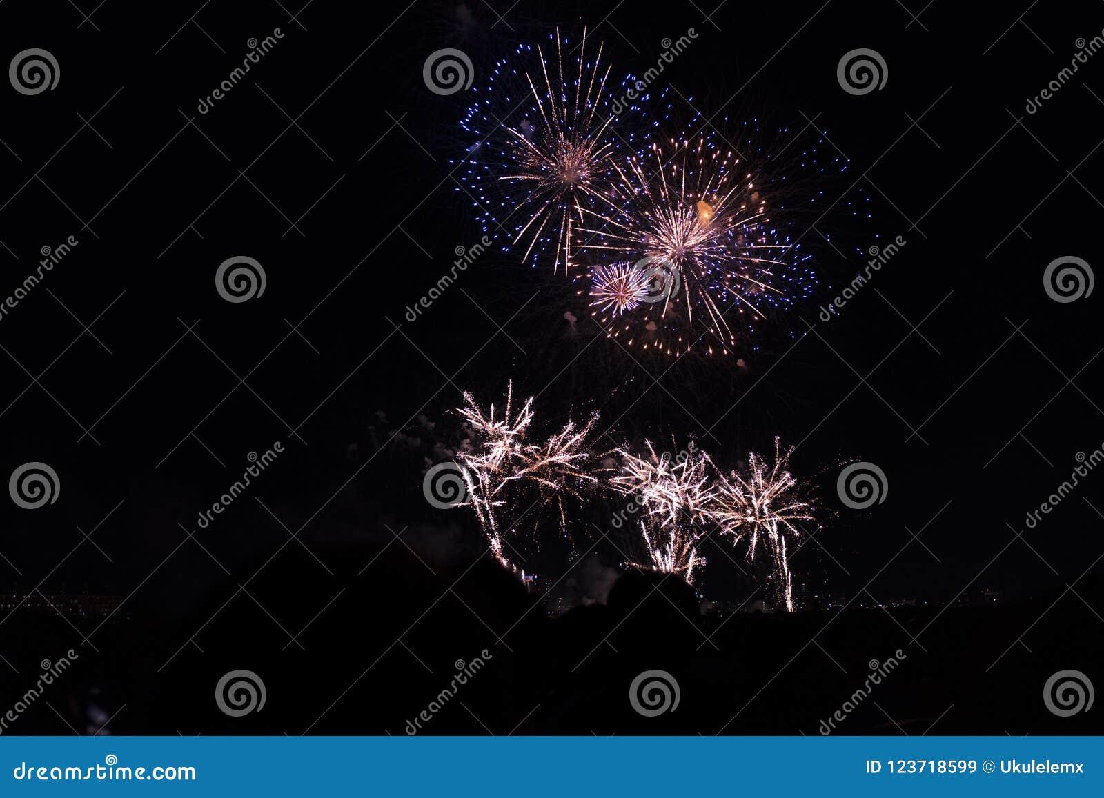 Veelvoudig Vuurwerk in nachthemel in een samenstelling in gouden en blauwe schaduwen