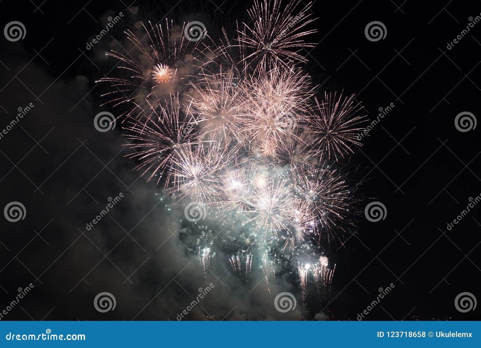 Veelvoudig Vuurwerk in nachthemel in een samenstelling in gouden en rode schaduwen