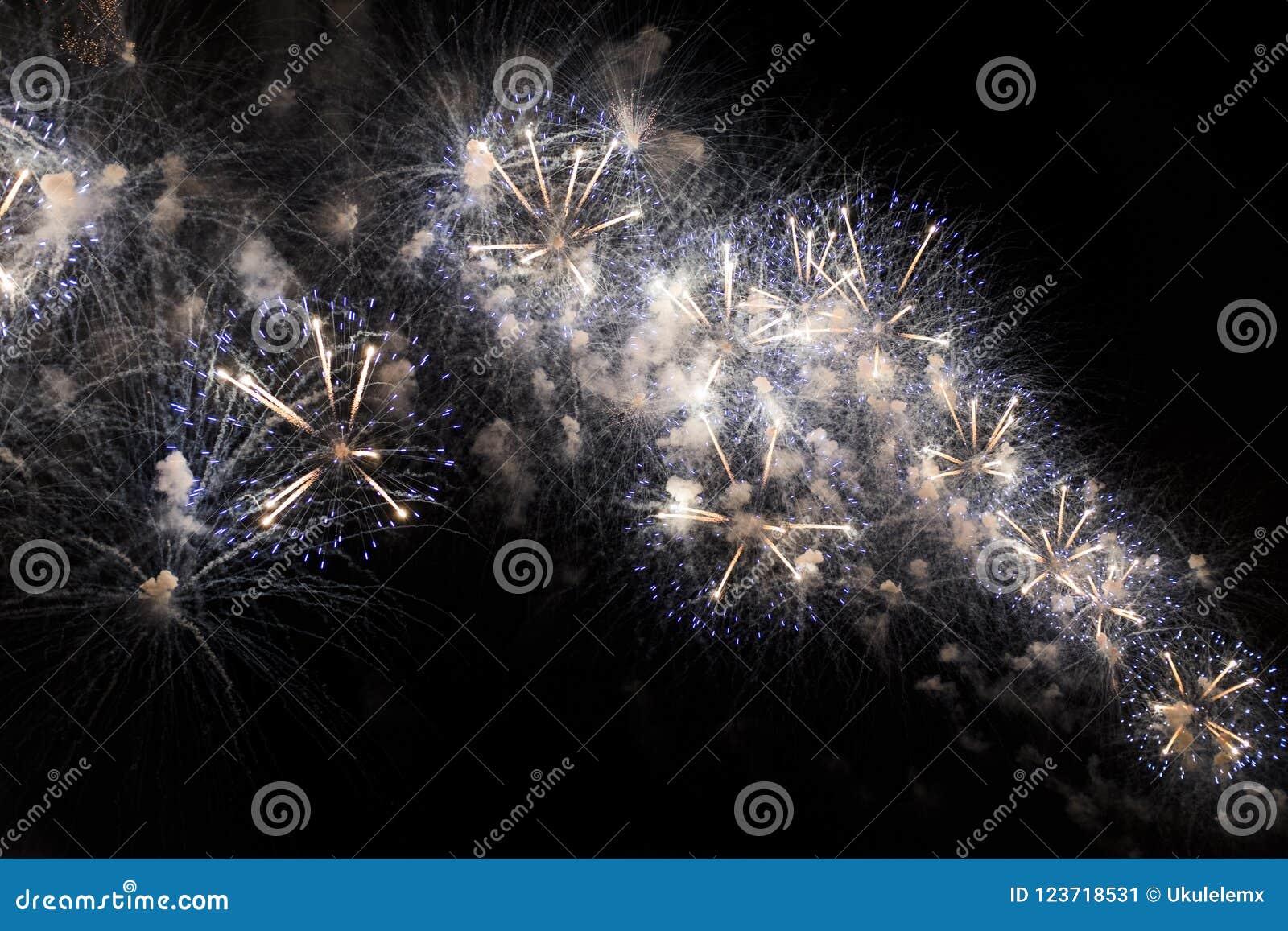 Veelvoudig Vuurwerk in nachthemel in een samenstelling in gouden en witte schaduwen
