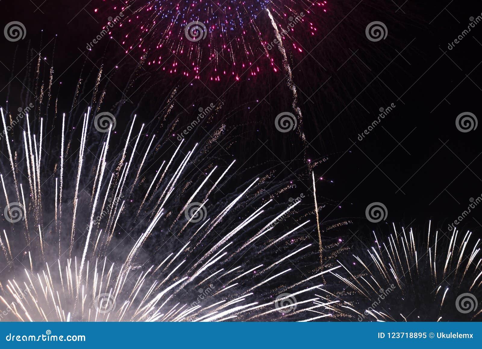 Veelvoudig Vuurwerk in nachthemel in een samenstelling in wit en rode schaduwen