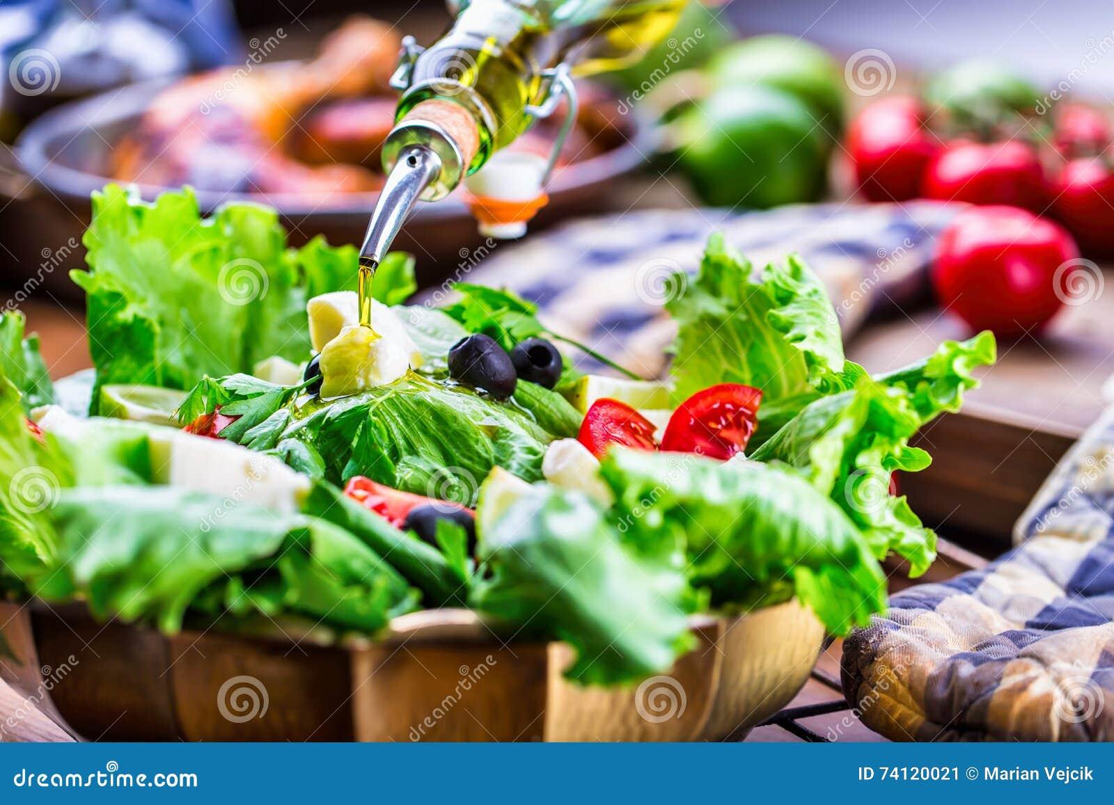Vegetable lettuce salad. Olive oil pouring into bowl of salad. Italian Mediterranean or Greek cuisine. Vegetarian vegan food