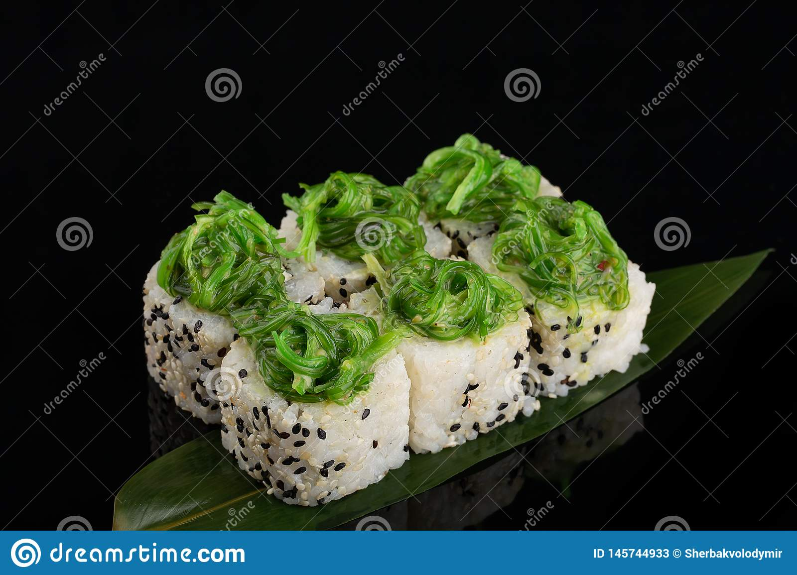 Vegetable maki rolls with seaweed on banana leaf at black background