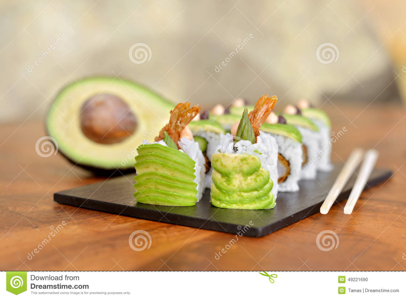 Vegetable sushi on black plate with avocado half and chopsticks. .