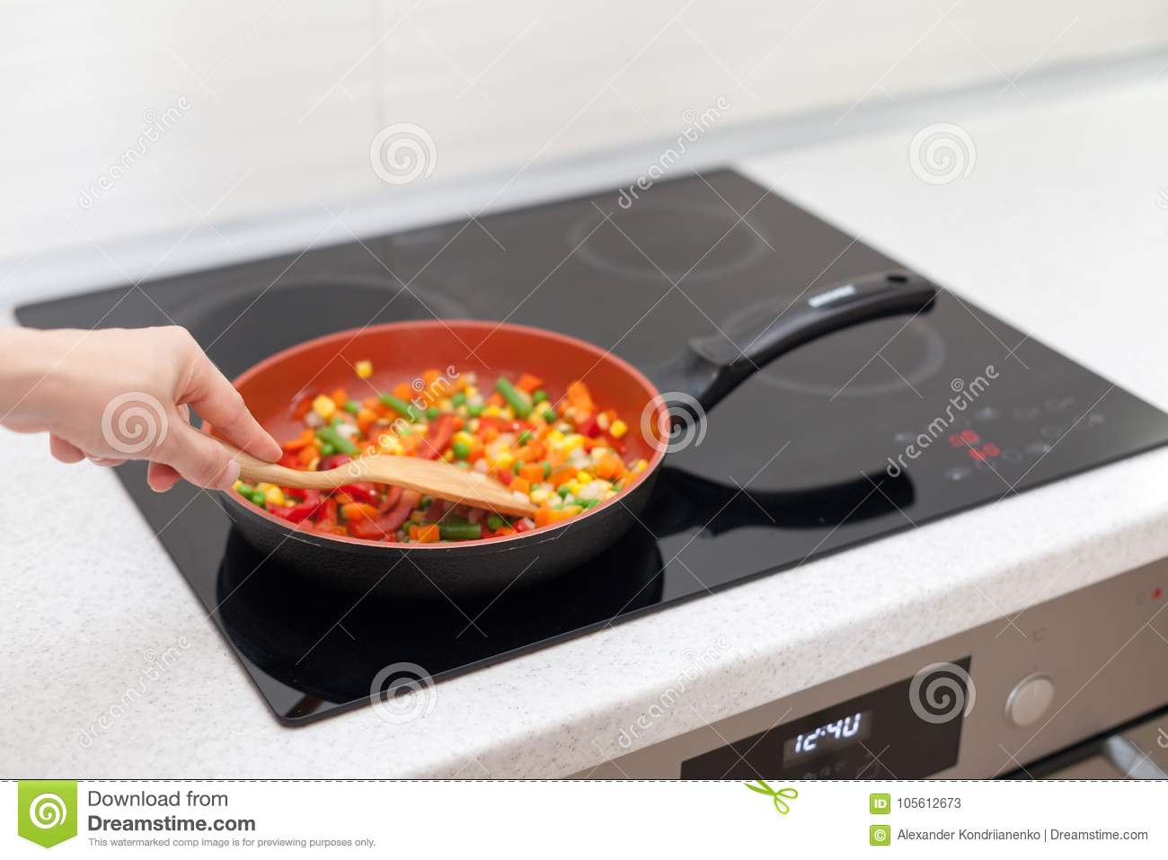 Vegetables are in a frying pan. Woman cooking colourful fresh vegetables on an electric stove.