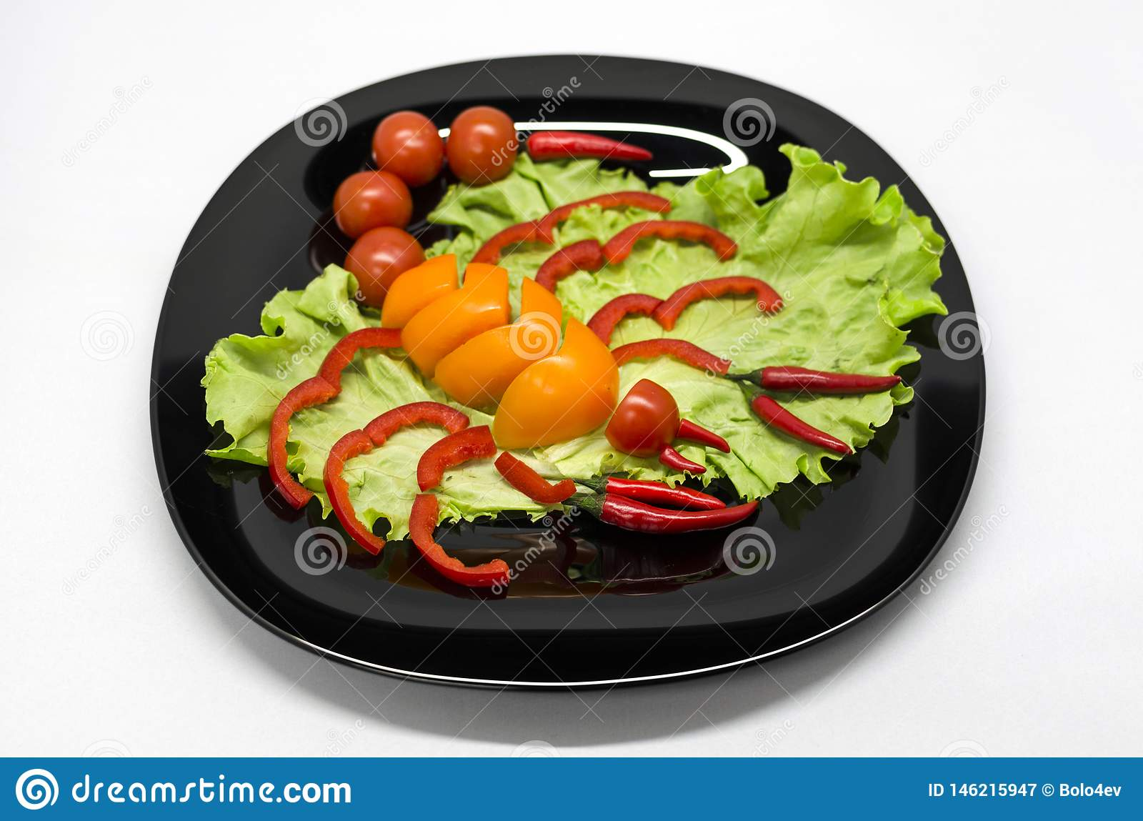 Vegetables on a plate laid out in the shape of a scorpion