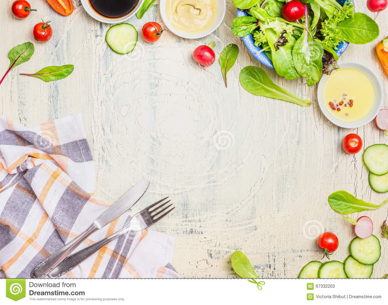 Vegetables salad preparation with dressings ,ingredients cutlery and kitchen checked napkin on light rustic background, top view