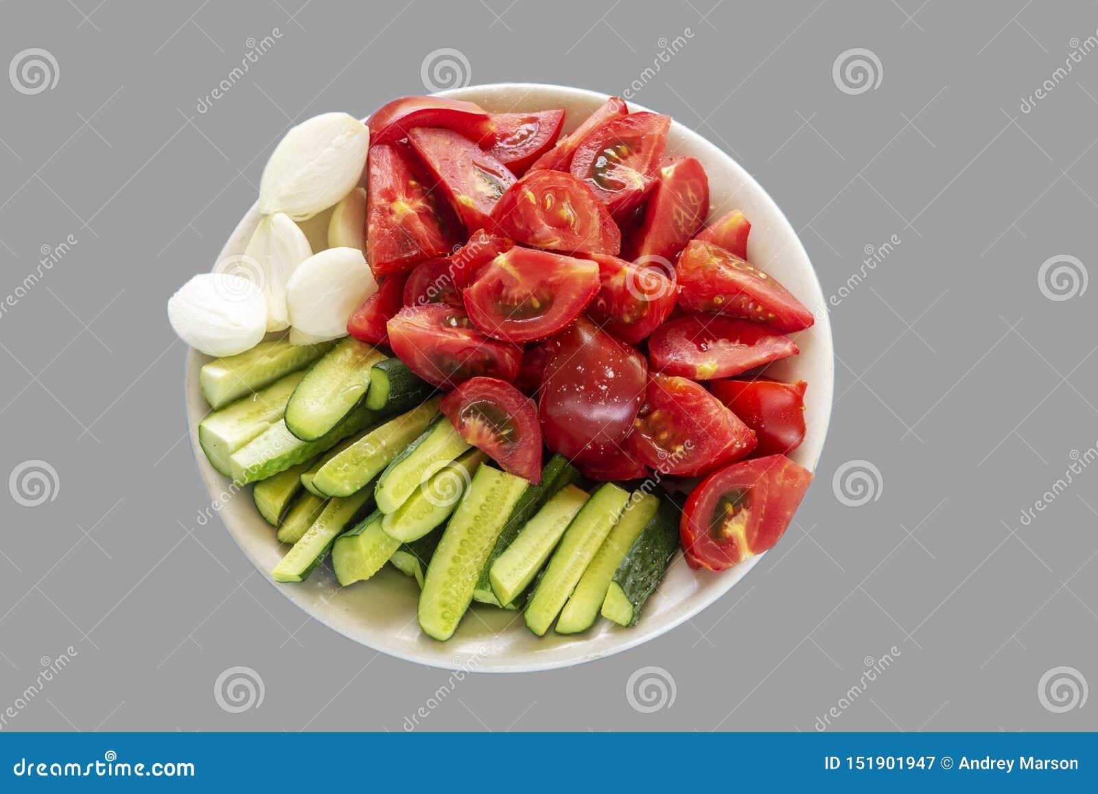 Vegetais cortados Tomates, pepinos e cebolas em um fundo cinzento Trajeto de grampeamento