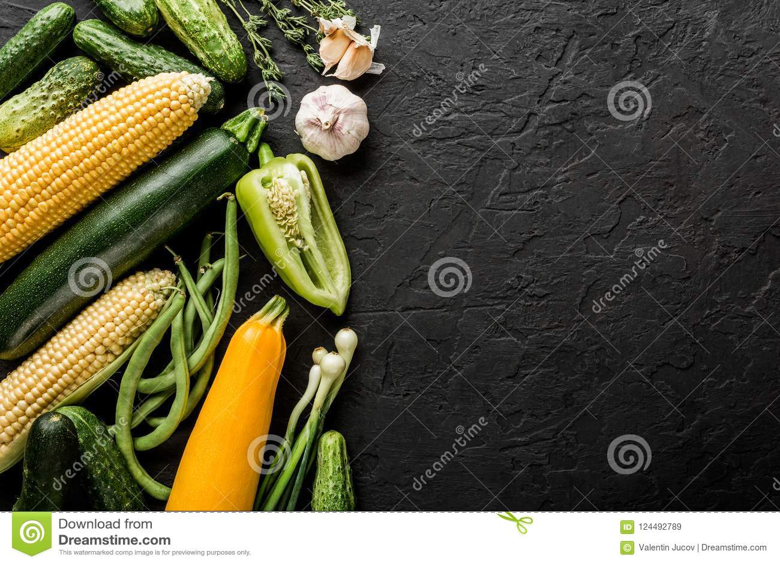 Vegetais do vegetariano do verão e ervas crus saudáveis, pepinos, milho, pimenta, abobrinha, feijões verdes no fundo de pedra pre