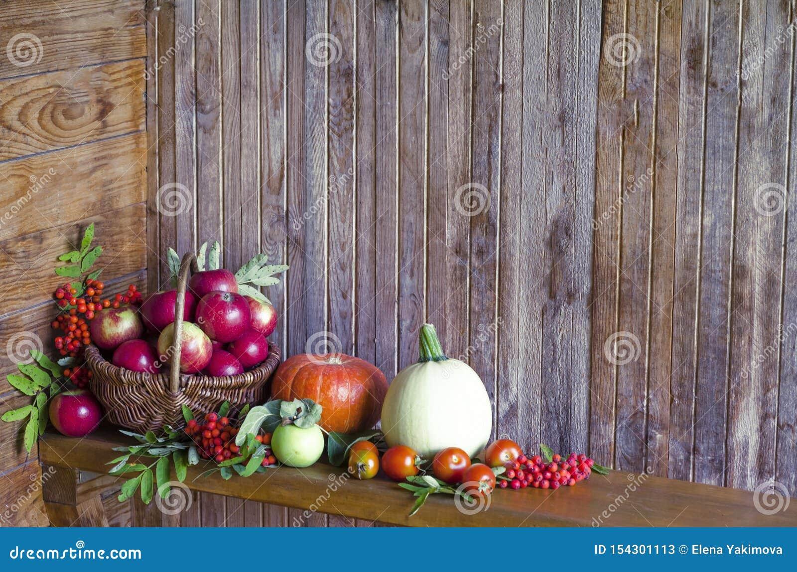 Vegetais e frutos em uma cesta em um fundo de madeira colhendo a abóbora da colheita do outono e do verão, abobrinha, maçã,