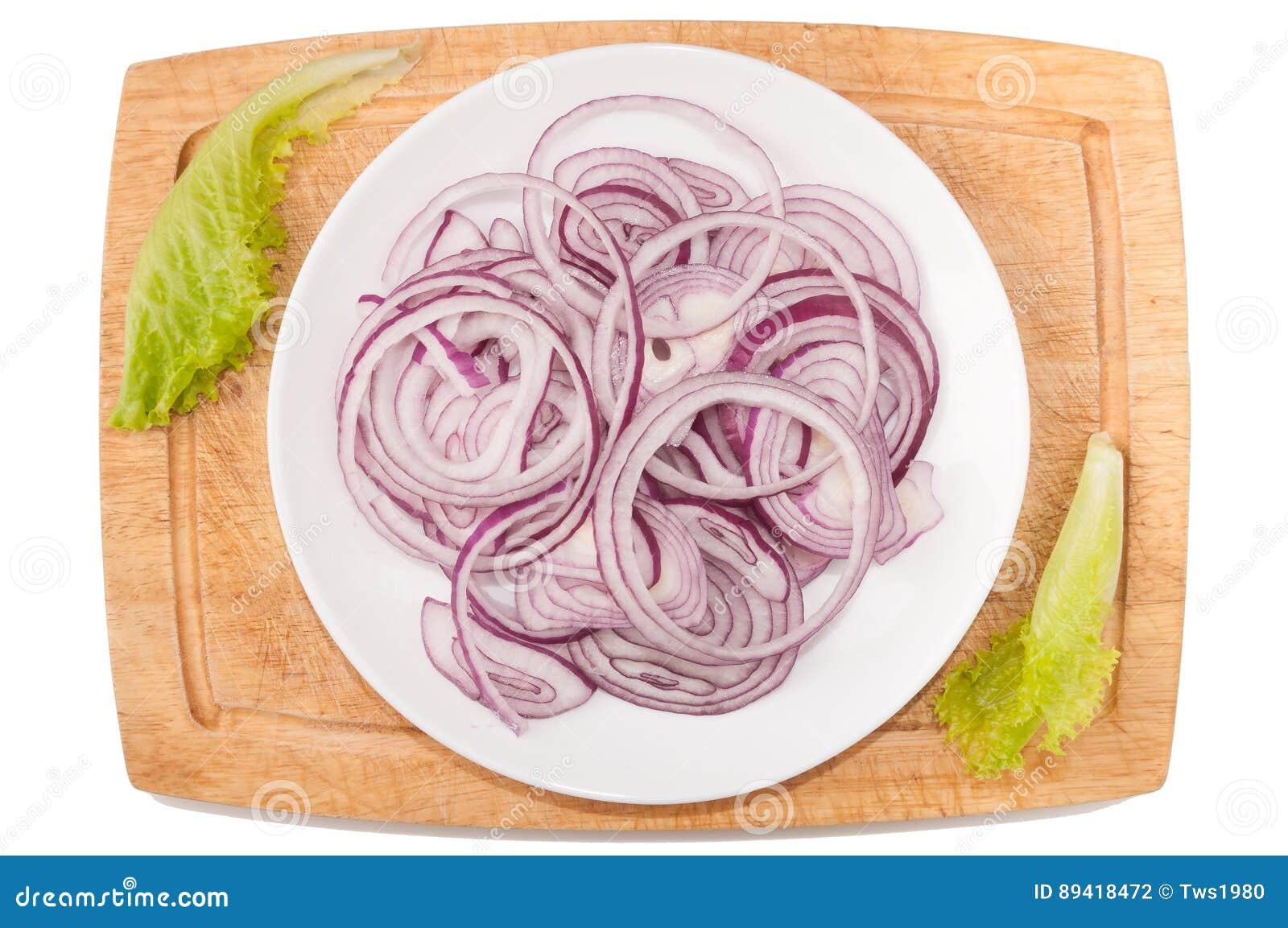 Vegetais no fundo branco Cebola, verdes, placa de corte, placa em um fundo branco