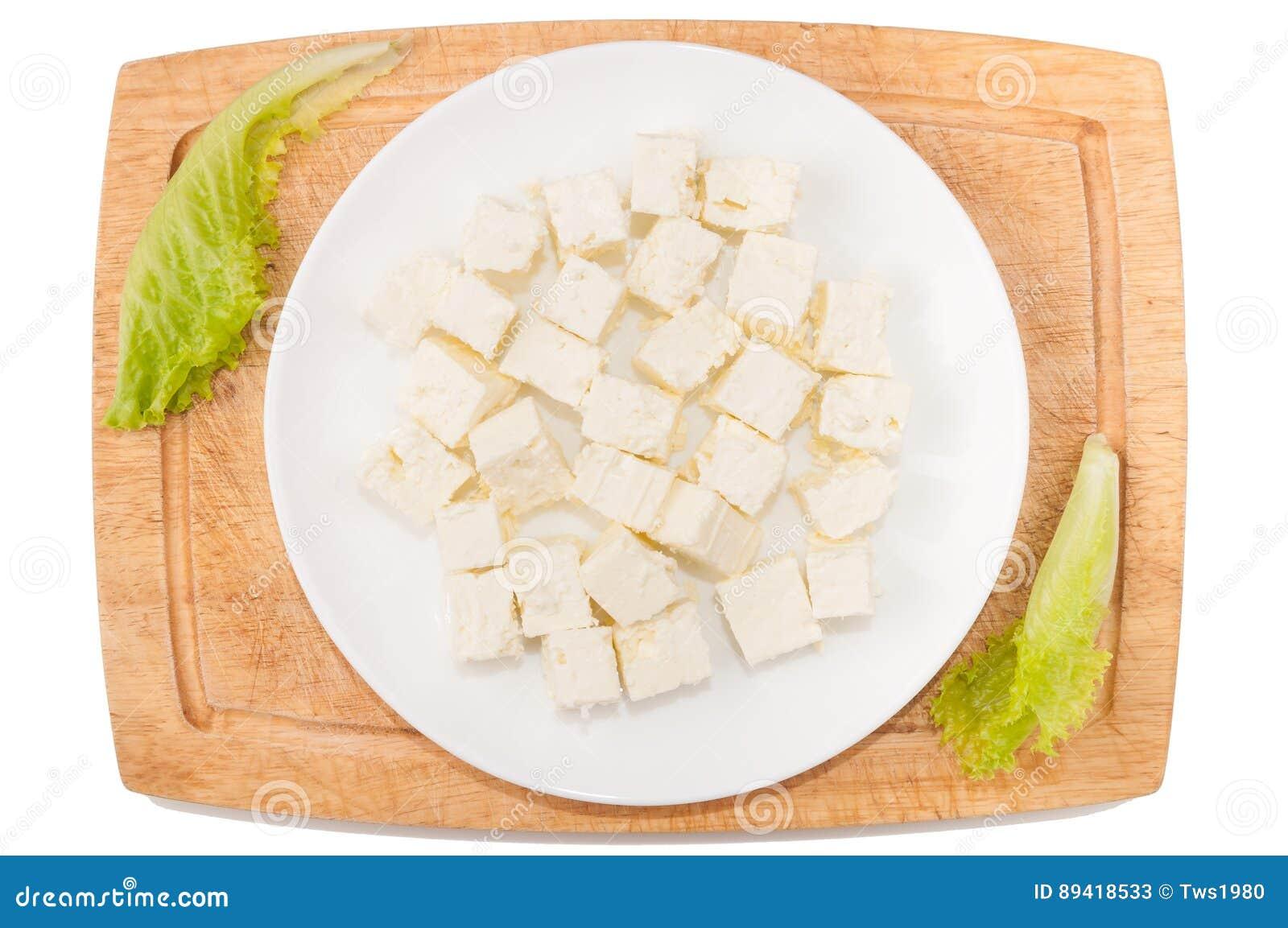 Vegetais no fundo branco Queijo de feta, verdes, placa de corte, placa em um fundo branco