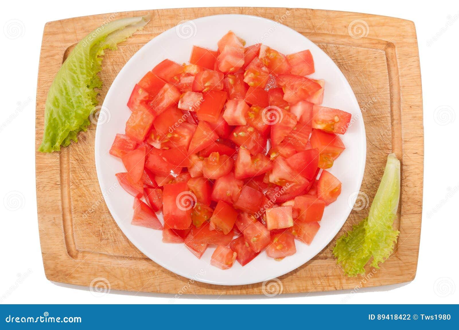 Vegetais no fundo branco Tomate, verdes, placa de corte, placa em um fundo branco
