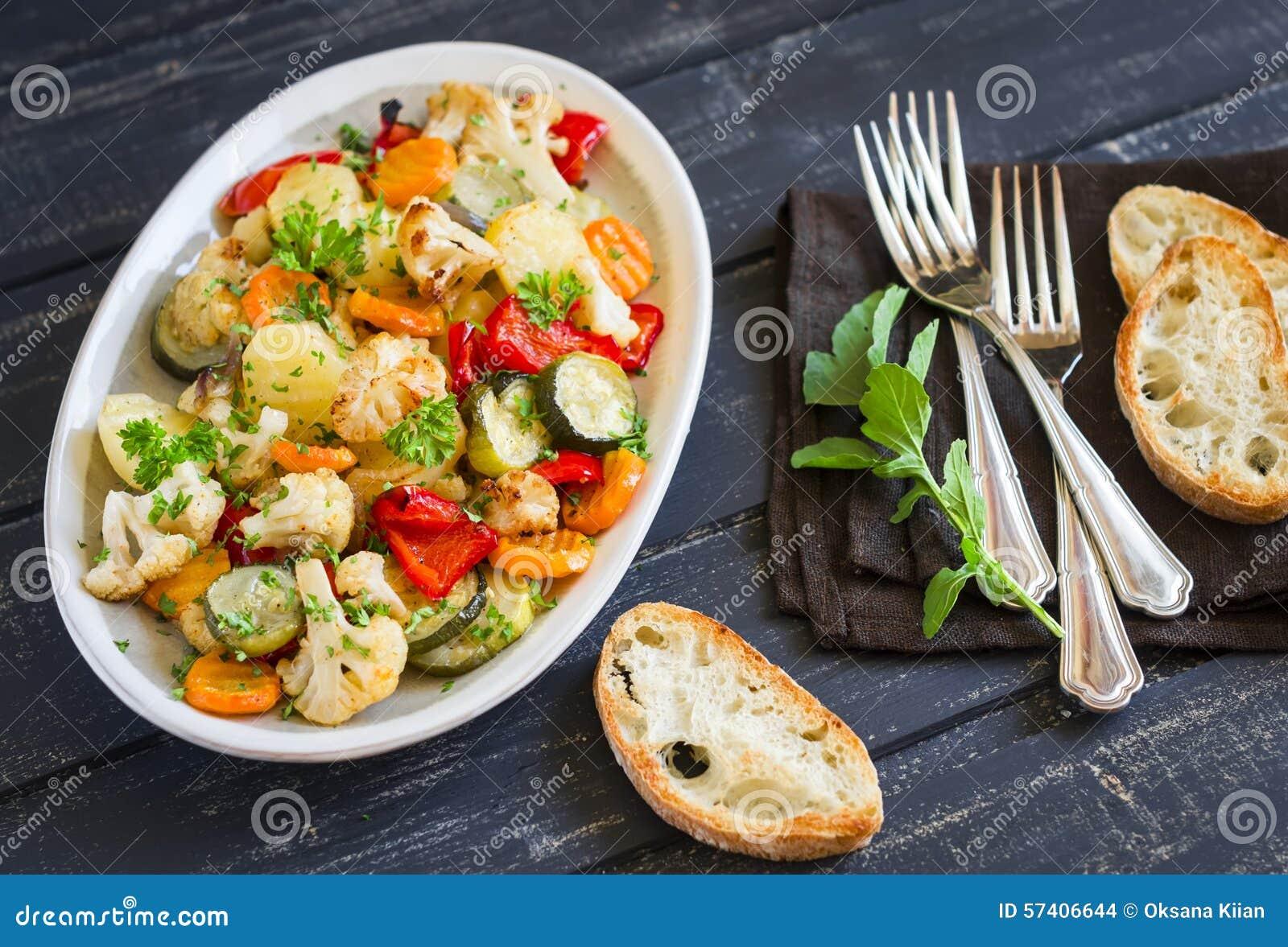 Vegetais Roasted - abobrinha, couve-flor, batatas, cenouras, cebolas, pimentas, em um prato oval