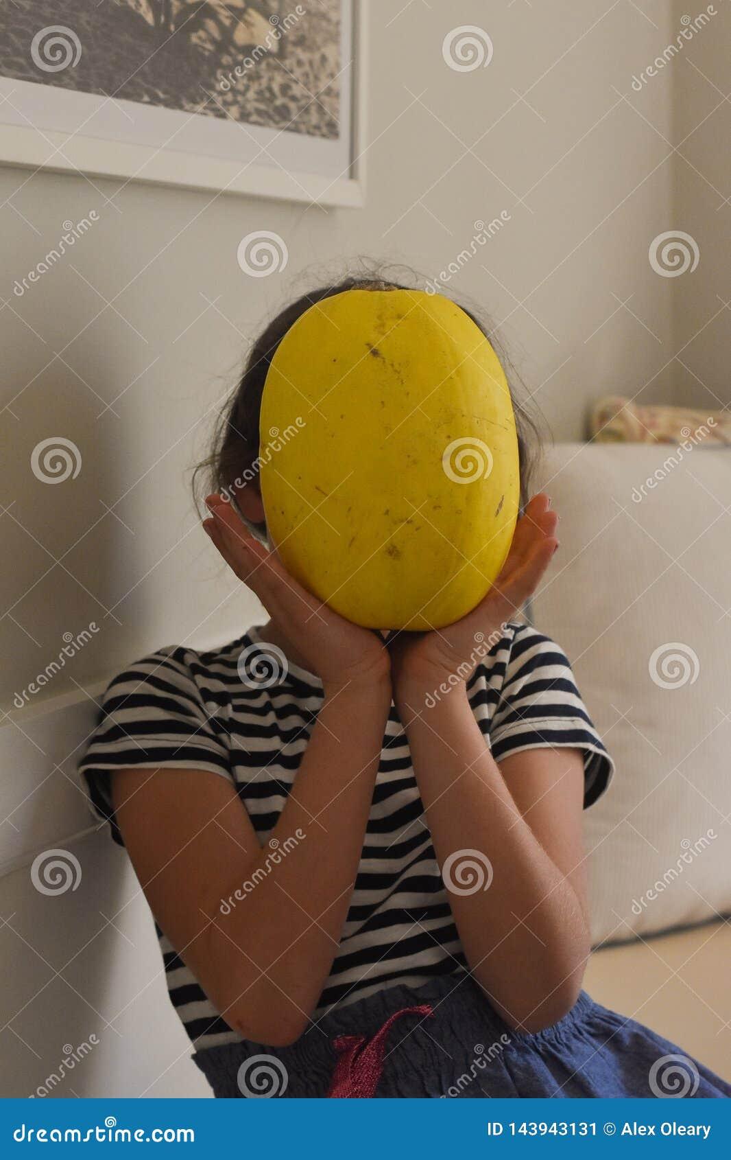 Vegetal da terra arrendada da moça na frente da cara em uma sala de visitas branca