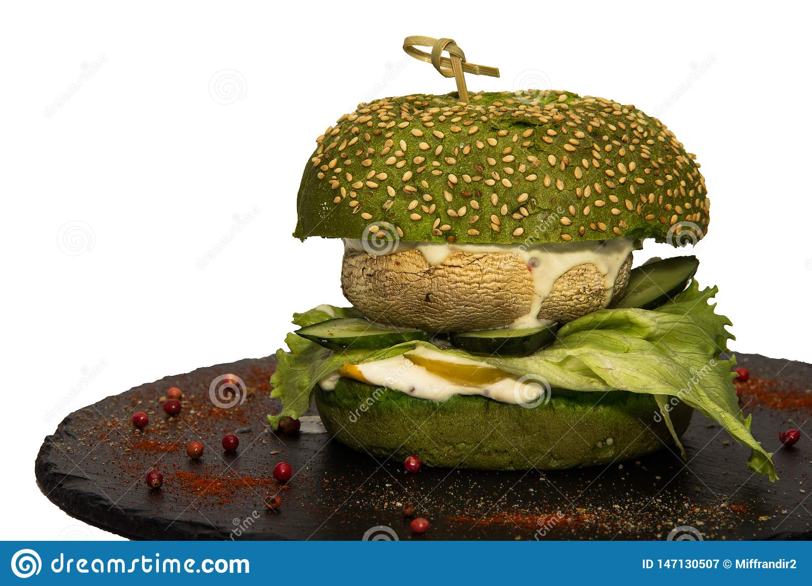 Vegetarian burger with a leaf of green salad, champignon, cucumbers and sauce.