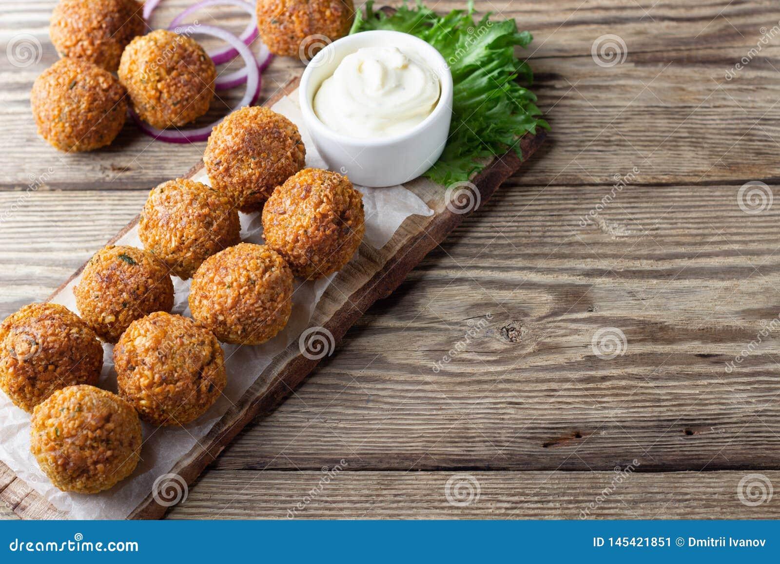 Vegetarian chickpeas falafel balls on wooden rustic board. Traditional arabian food