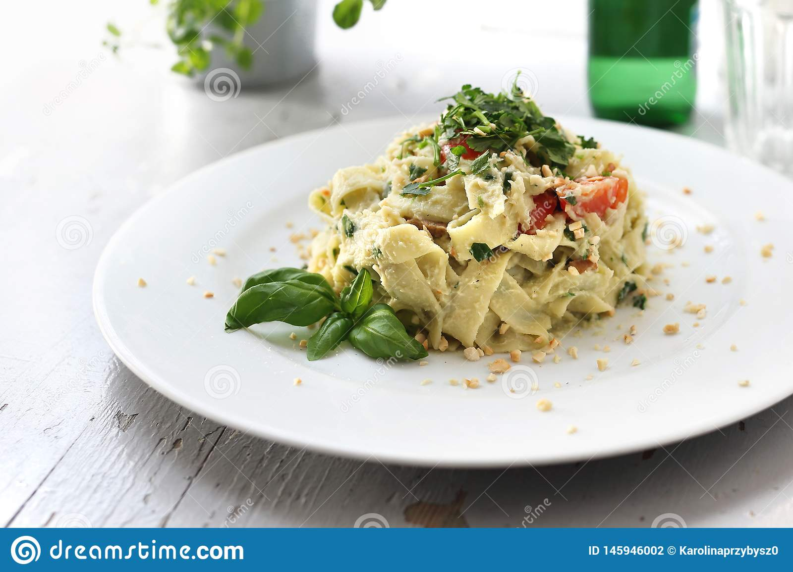 Vegetarian cooking. Pappardelle pasta with cauliflower and spinach. Dish on a white plate