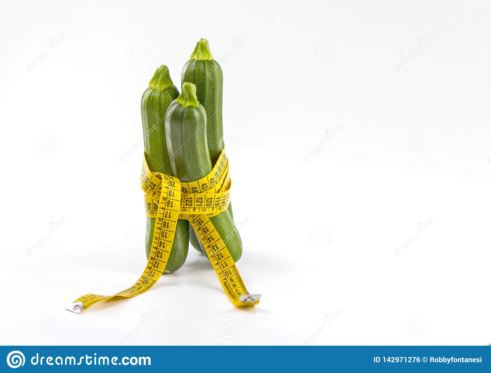 Vegetarian diet to reduce weight. Three freshly picked courgettes wrapped in a body measuring tape ruler that symbolizes the