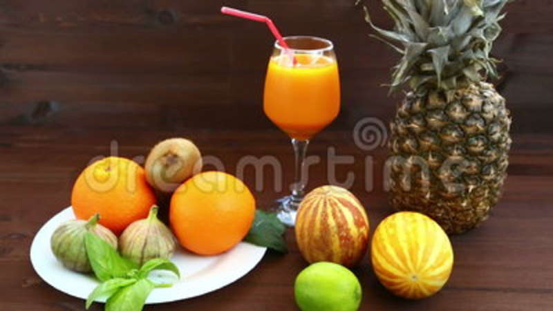 Vegetarian diet  On a white plate are Vietnamese melon, juice, figs,  oranges, pineapple  Glass, mint