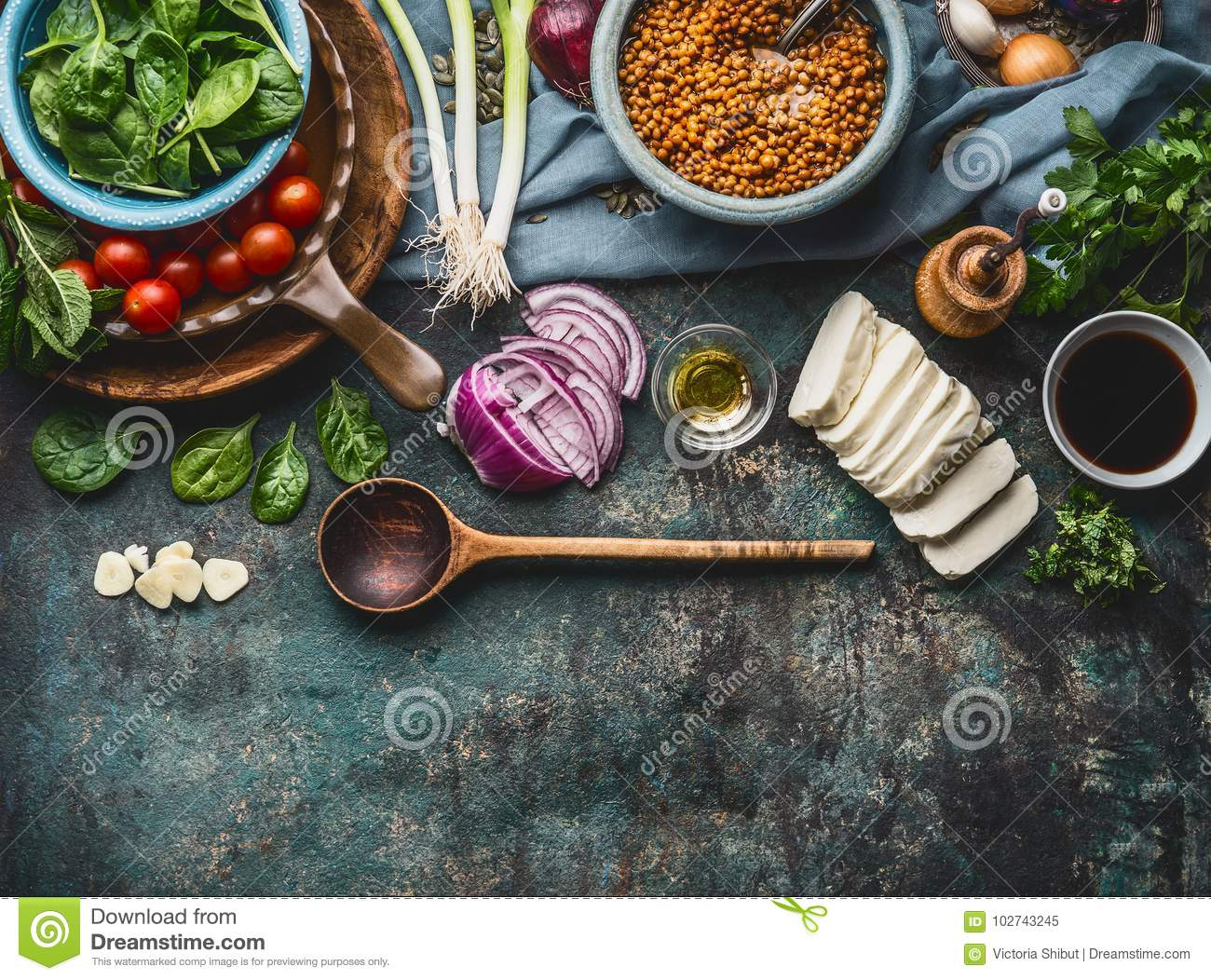 Vegetarian ingredients for tasty lentil dishes on rustic kitchen table background with cooking spoon and utensils, top view, borde