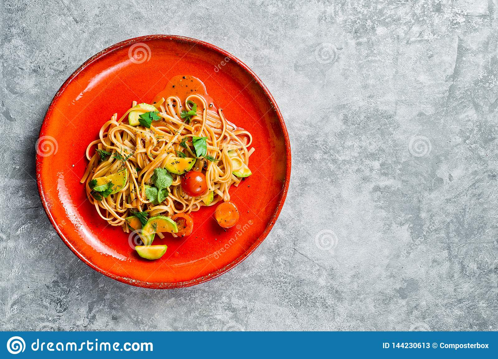 Vegetarian pasta with tomatoes, avacado and squash. Gray background, top view, space for text.