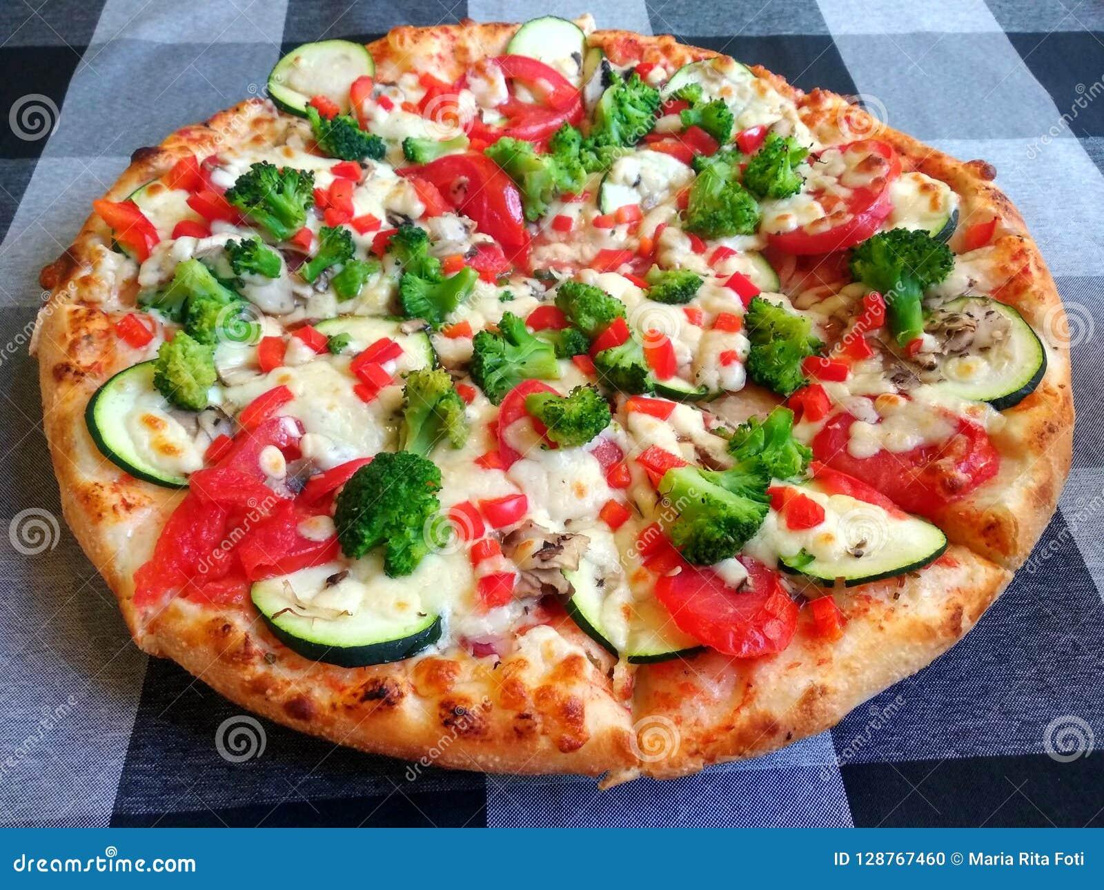 Vegetarian pizza with broccoli, zucchini, tomato, pepper and mozzarella on a checked table cloth