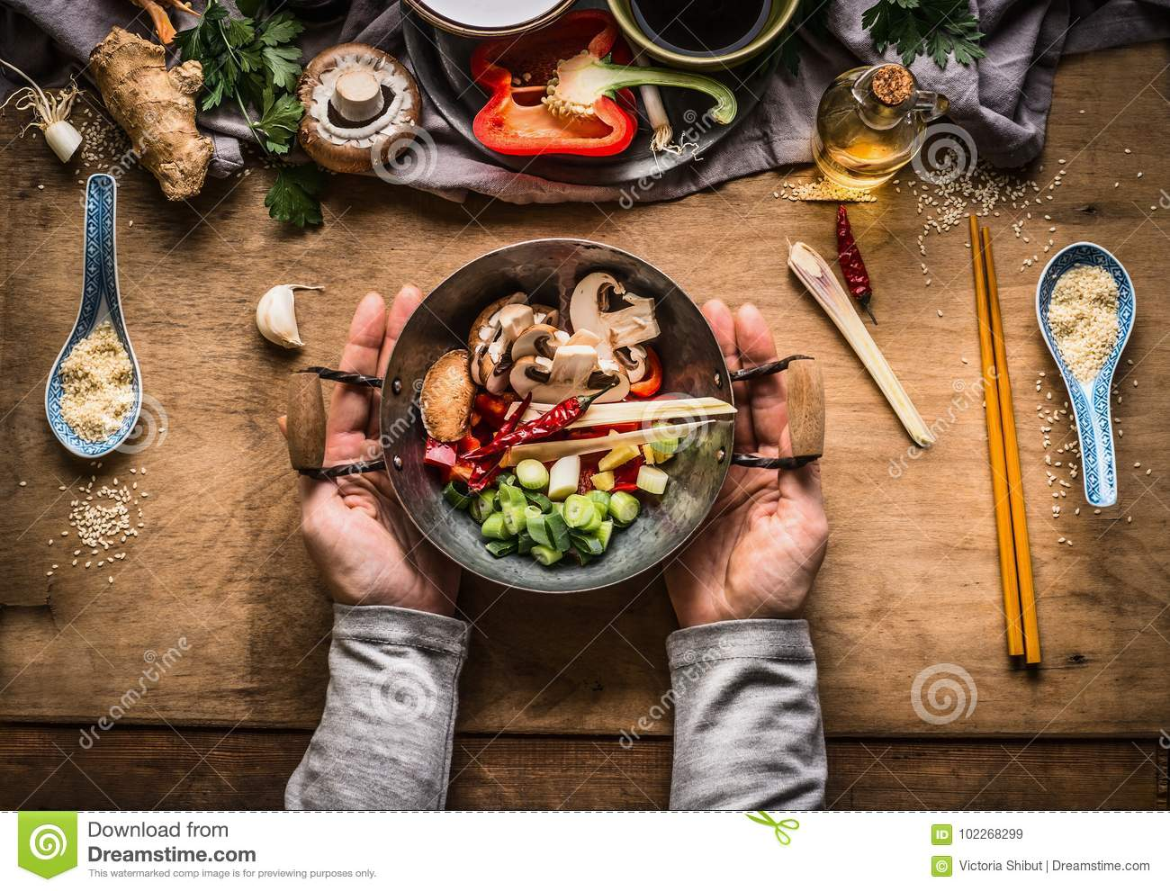 Vegetarian stir fry cooking preparation. Women female hands holding little wok pot with chopped vegetables for stir fry on kitchen