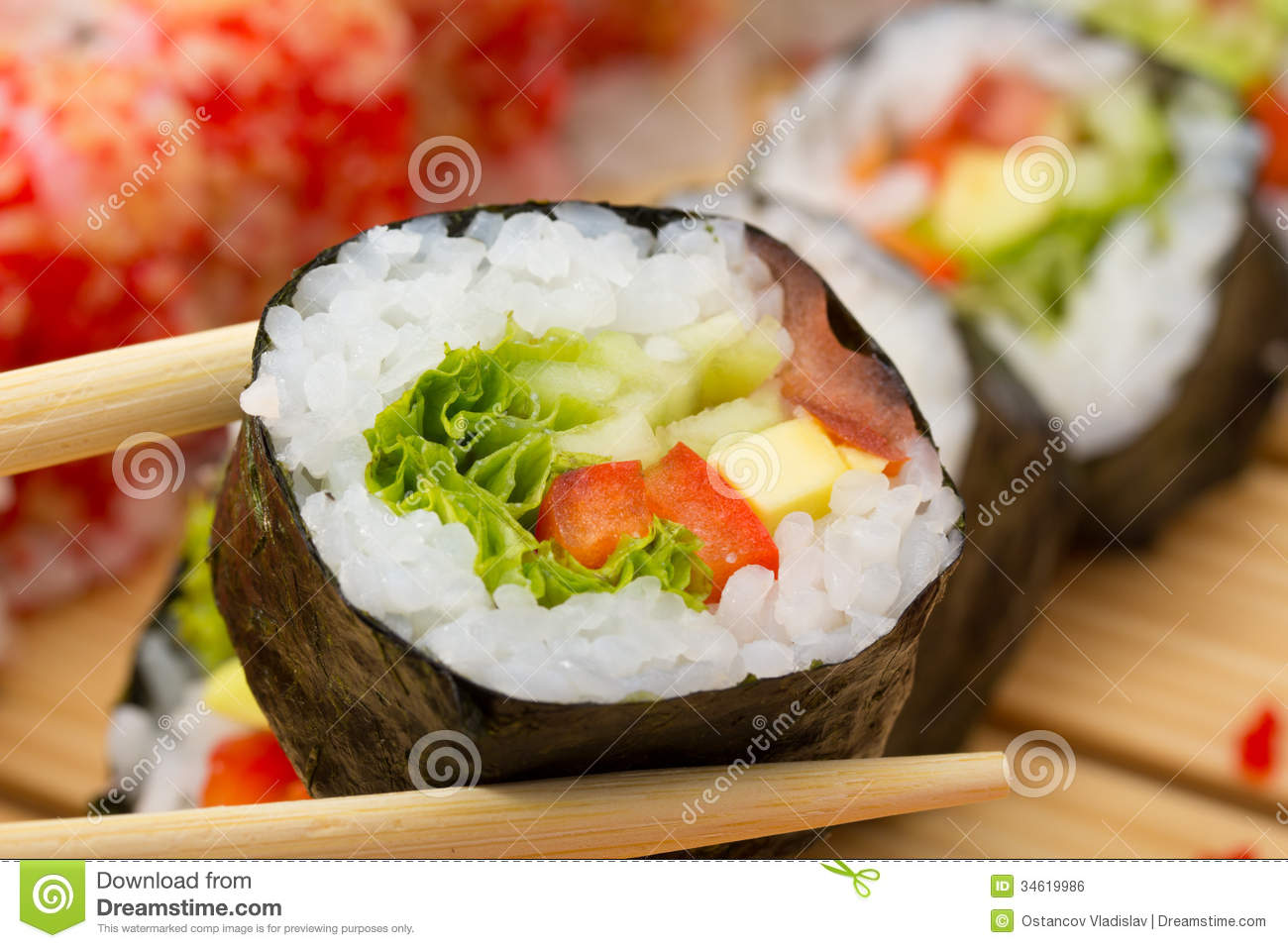 Vegetarian sushi roll in chopsticks with sushi made dish on background ...