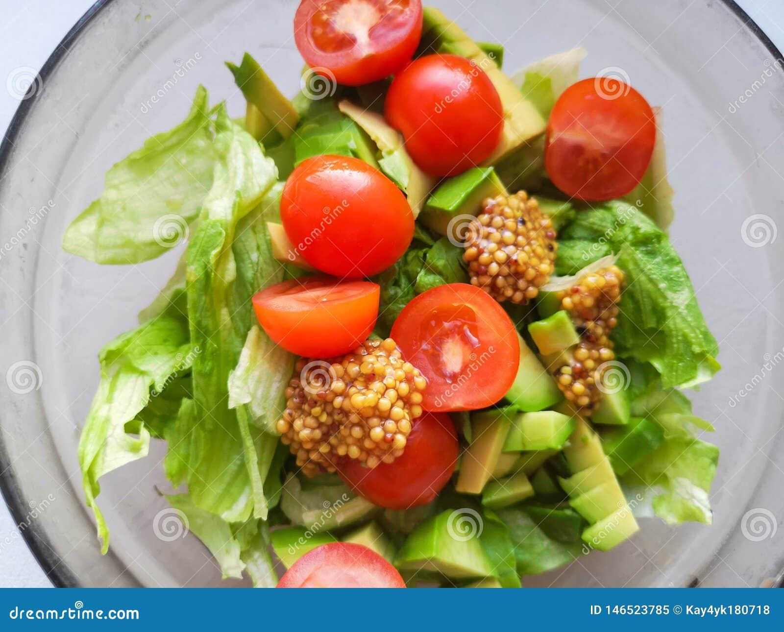 Vegetarian vegetable salad. Fresh salad flying to bowl in super slow motion. Avocado Tomato Salad