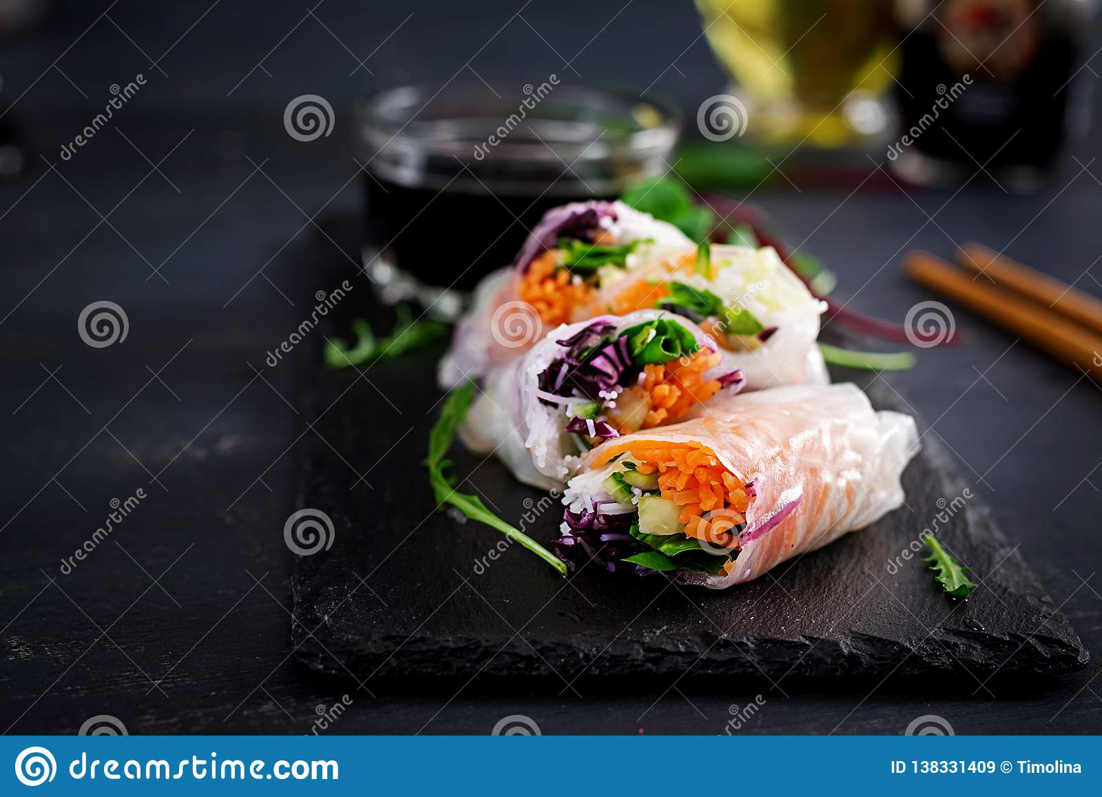 Vegetarian vietnamese spring rolls with spicy sauce, carrot, cucumber