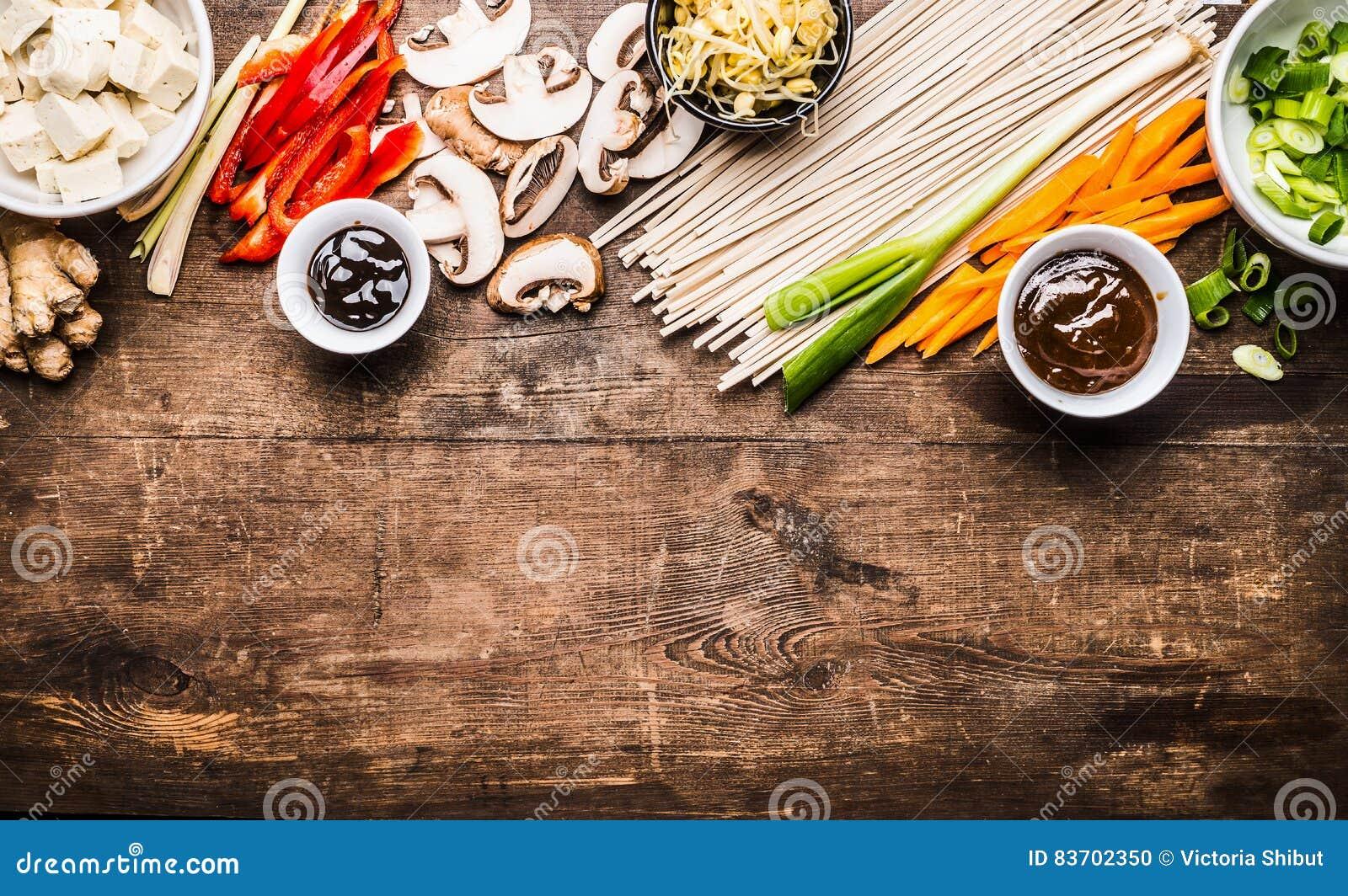 Vegetariano asiático que cozinha ingredientes para a fritada da agitação com tofu, macarronetes, gengibre, vegetais cortados, bro