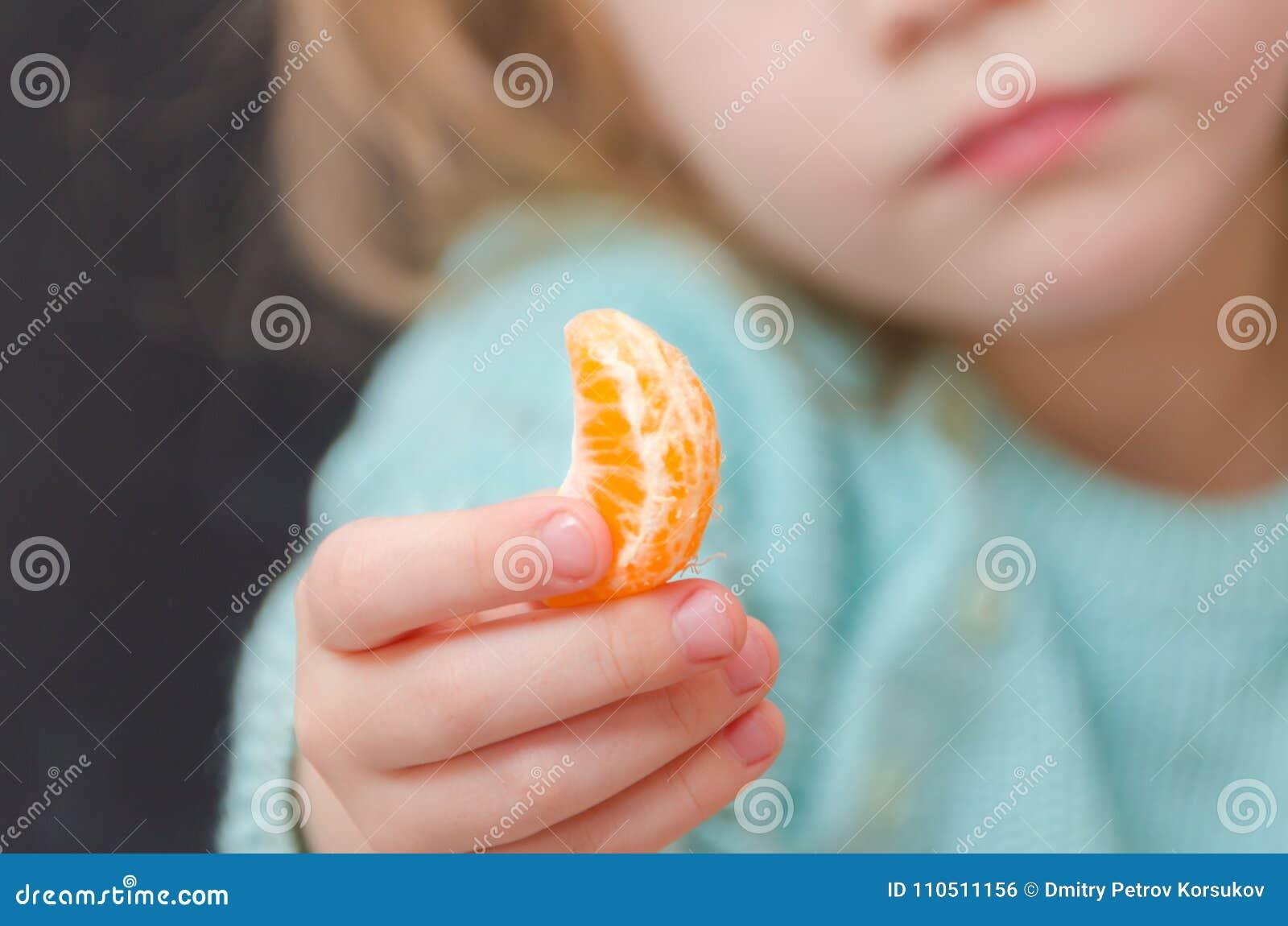 Vegetariano del bebé con la rebanada del mandarín