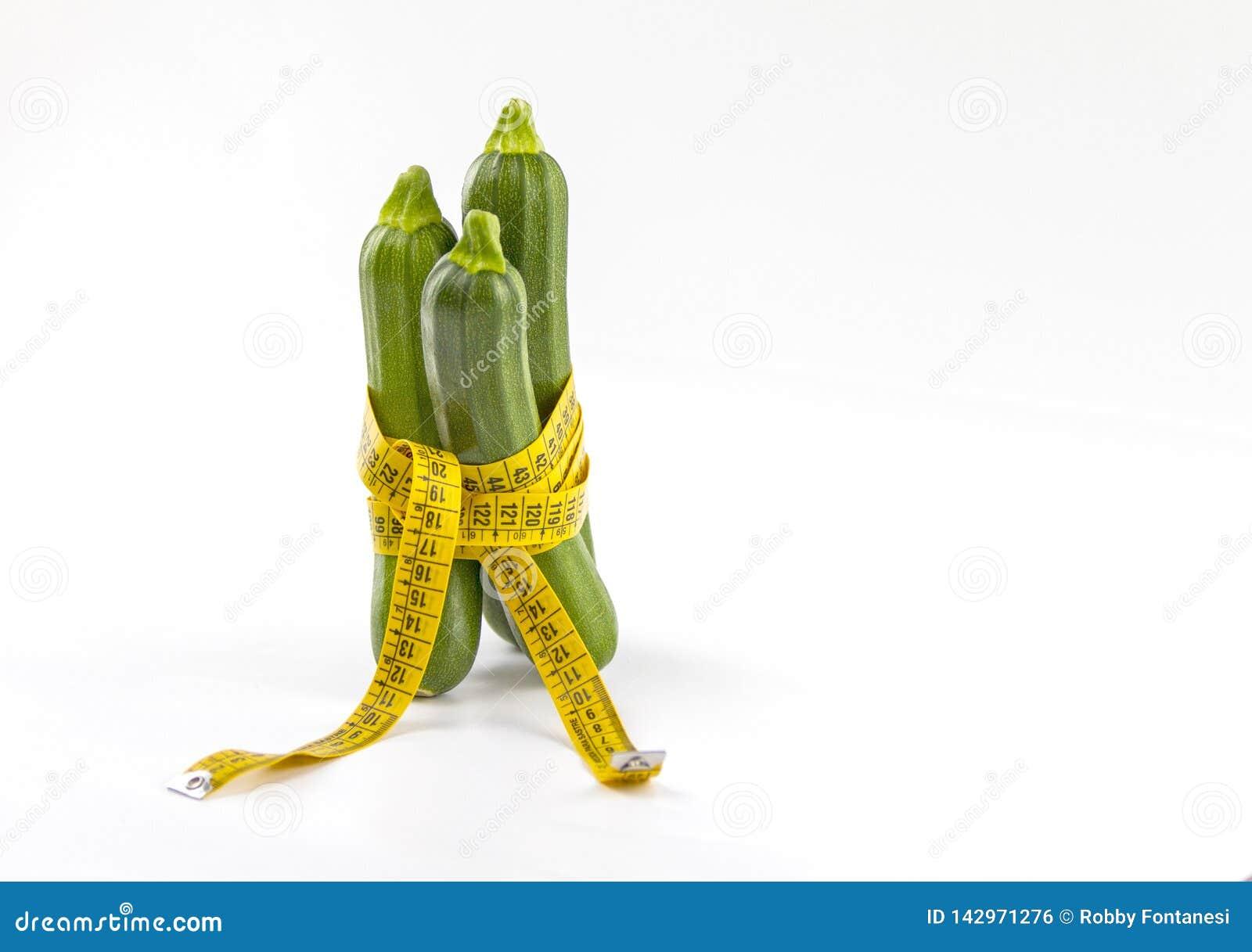 Vegetarisch dieet om gewicht te verminderen Drie vers geplukte die courgettes in een lichaam worden verpakt die bandheerser meten