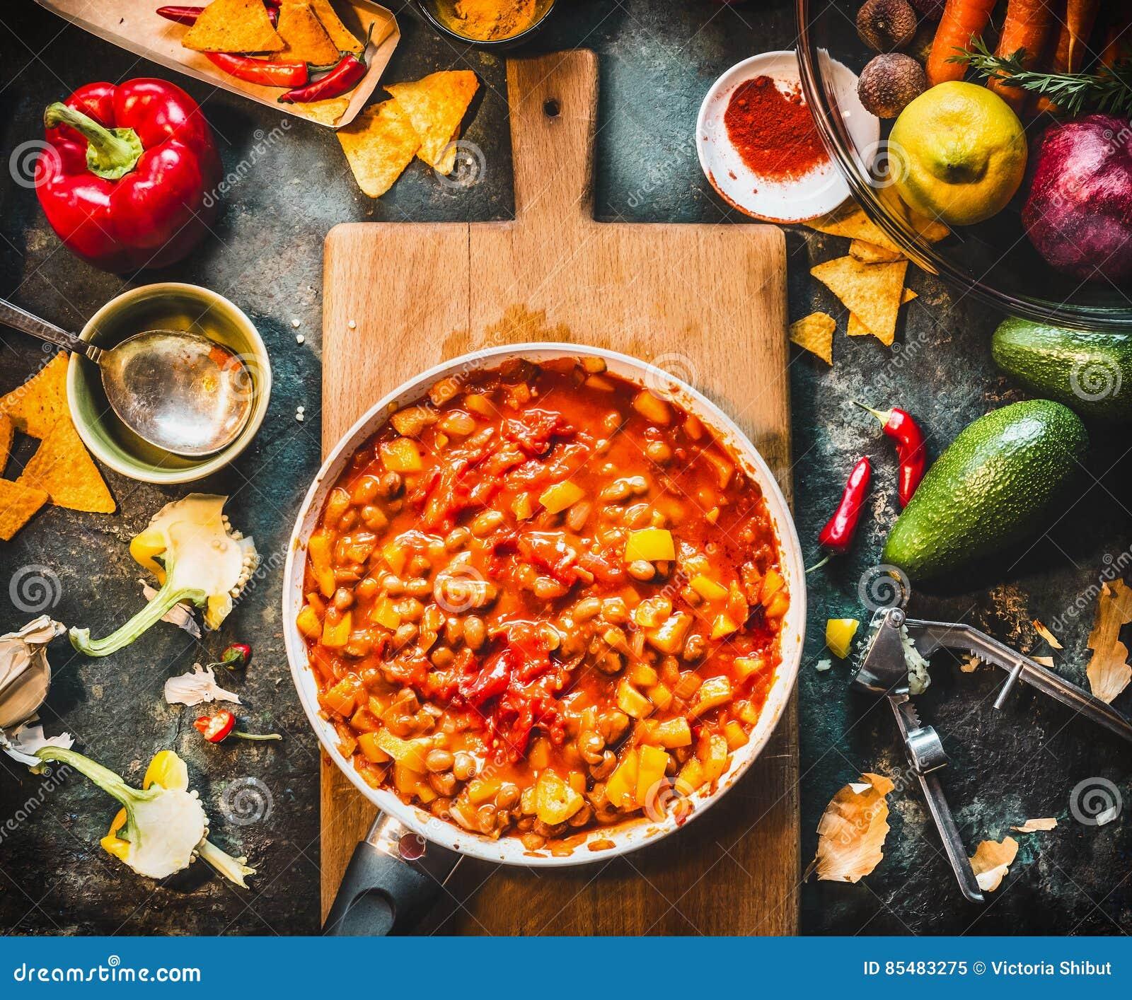 Vegetarische chili con carneschotel in pan op houten scherpe raad met kruiden en groenten die ingrediënten op donkere keuken koke